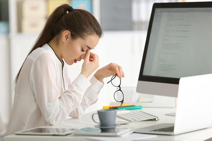 デスクワーク中に目元を押さえている女性の画像