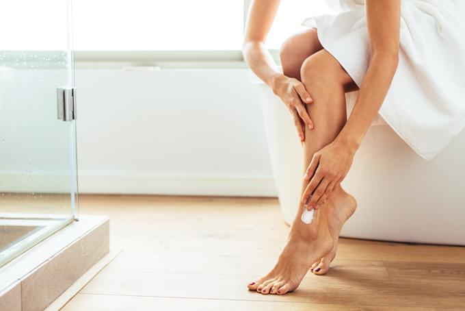 お風呂上がり脚の保湿をしている女性の脚元画像