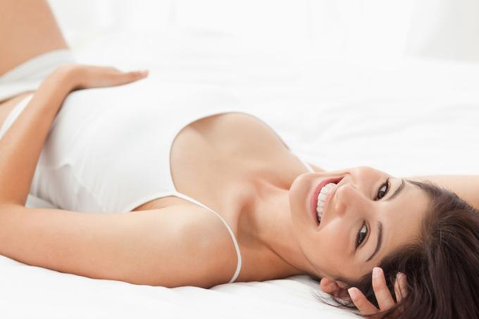 ベッドの上でお腹の上に手を置き、笑顔の女性