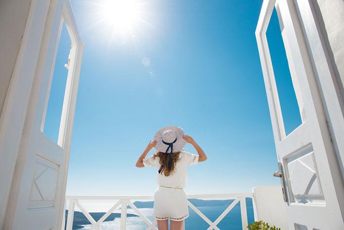 海が見える家のベランダに立っている女性の後ろ姿画像