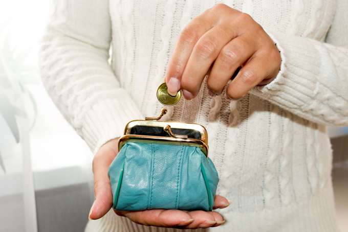 小銭をがま口に入れている女性の手元画像