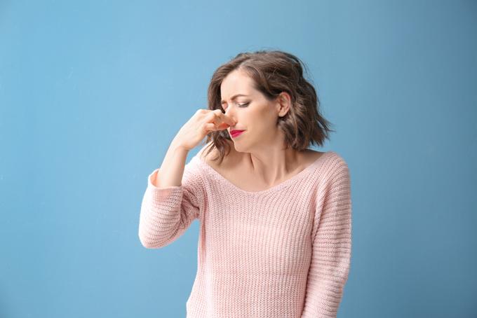 鼻をつまんでいる女性の画像