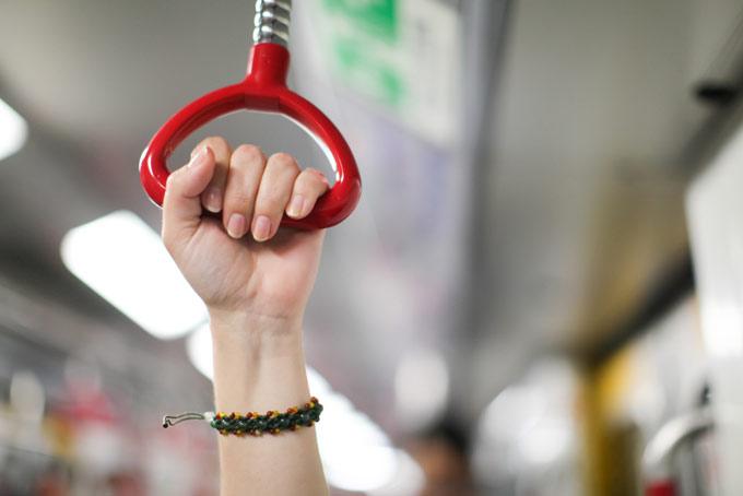 電車の手すりをつかんでいる手の画像
