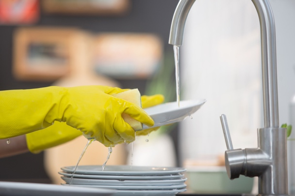 家庭用手袋をして食器洗いをする人