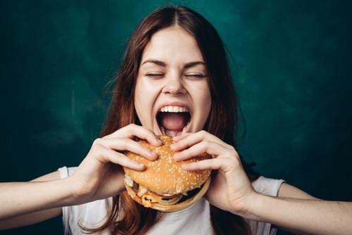 ハンバーガーにかぶりつく女性