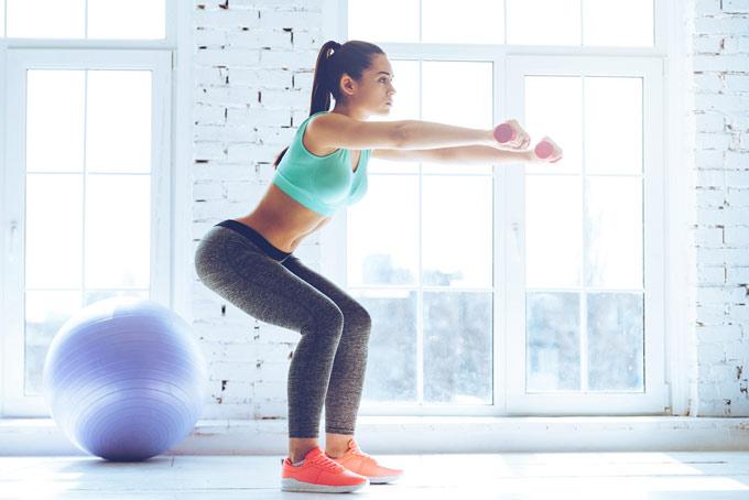 腕を前に上げてお尻のトレーニングをする女性の画像