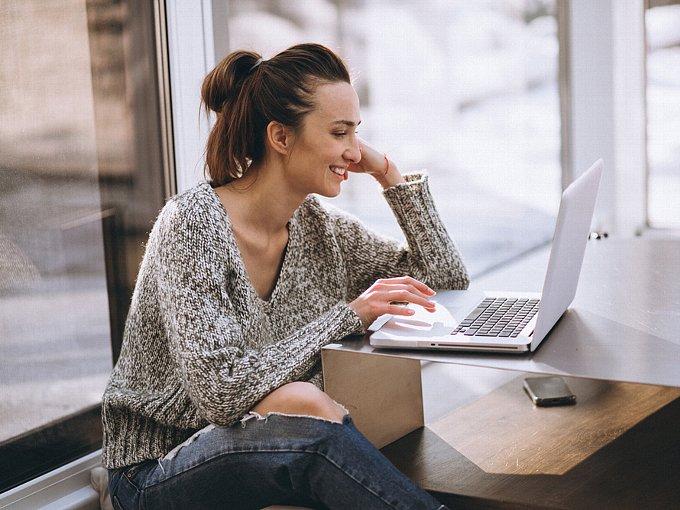 Vネックのニットを着てパソコンを眺める女性