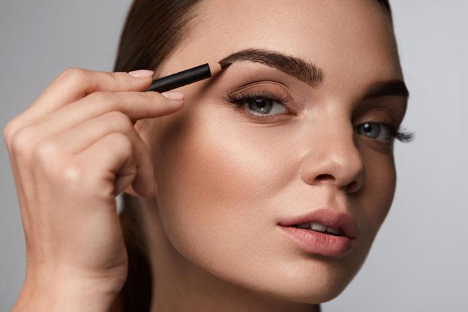 眉毛を書いている女性の画像