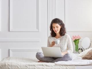 ベッドの上でパソコンを見る女性