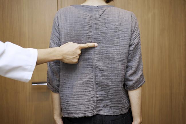 肩甲骨を指している写真