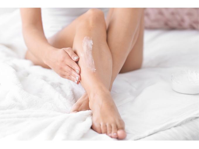 脚にクリームを塗っている女性の脚画像