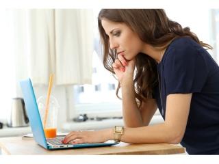 真面目な顔でパソコンを見つめる女性の画像