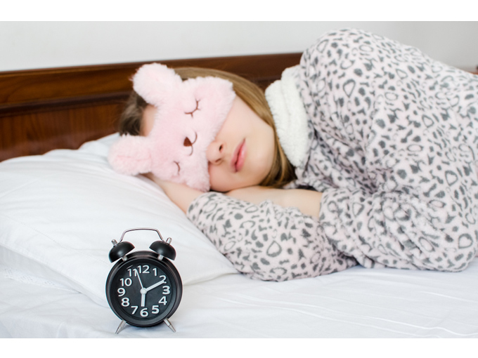 ベットの上でアイマスクをして寝ている女性の画像