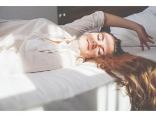 気持ちよさそうに二度寝する女性