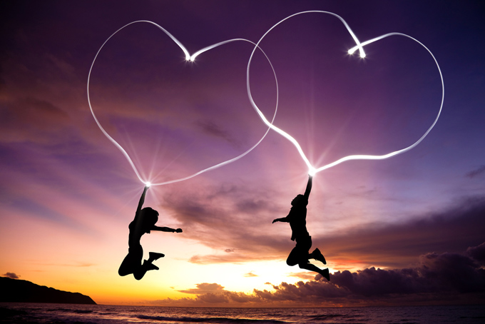 ジャンプしている男女の手から光のハートが空に作られている画像