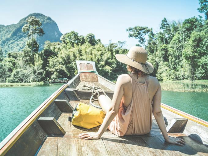 ボートの上に麦わら帽子をかぶった女性の画像