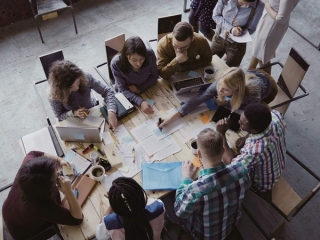 仕事のチームメンバーで集まって会議をしている画像