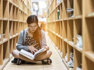 あぐらをかいて本に集中している女性の画像