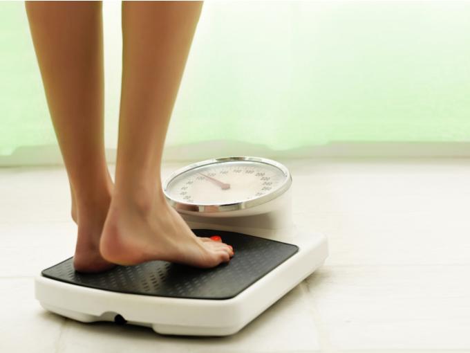 体重計の上に乗っている女性の画像
