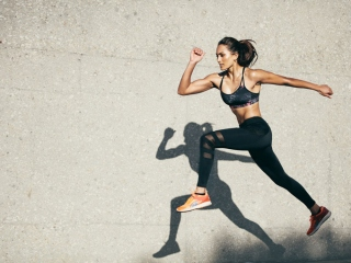 足を高く上げトレーニングする女性の画像