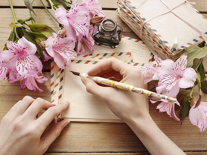ペンで文字を書こうとしている女性の手元