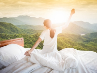 起床時に伸びをしている女性の画像