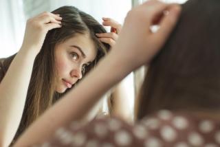 女性が髪の毛の生え際を鏡でチェックしているイメージ画像
