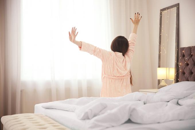 パジャマを着た女性が手をあげて伸びをしている後ろ姿画像