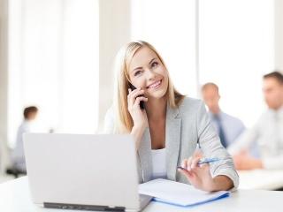 パソコンの前で笑顔で電話する女性