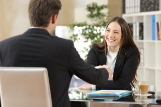 スーツを着た男女がデスクに座って握手している画像