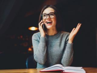 笑顔で電話をしている女性の画像