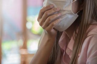 マスクをしてせきをする女性