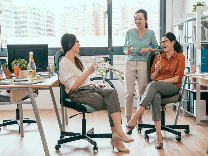 オフィスで楽しく話をしている女性の画像
