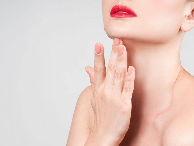 顎に指をあてて首を伸ばしている女性の画像