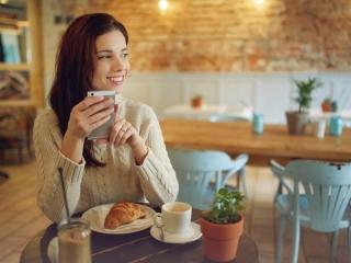 食事しながらスマホをもつ女性の画像
