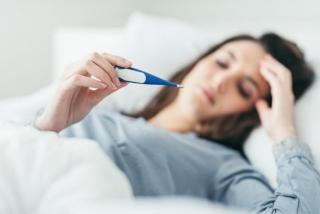 熱を体温計ではかる女性