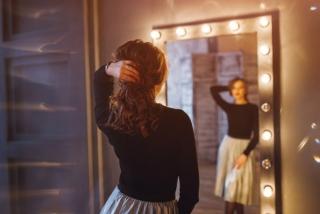 鏡の前で全身をチェックする女性