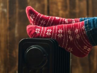 小型ヒーターの上で足を温める女性