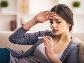 体温計で熱をはかる女性
