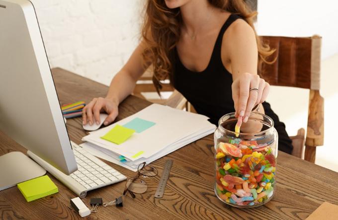 仕事しながら、お菓子に手をのばす女性