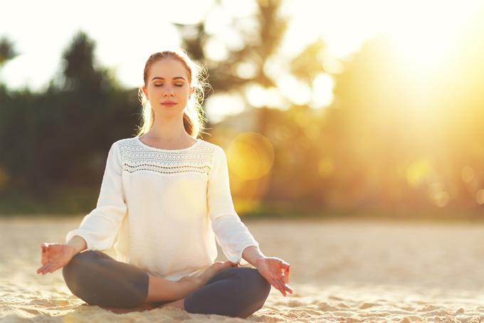 砂浜で瞑想する女性の画像