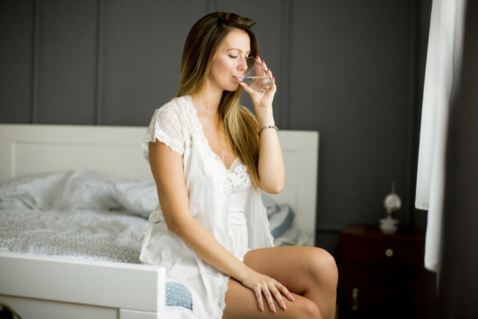 起き抜けに水を飲む女性