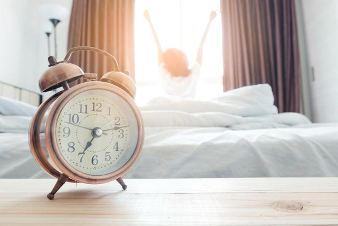 7時過ぎに起きて伸びをする女性