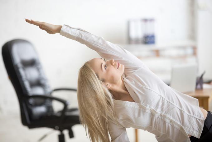オフィスでイスに座って体側を伸ばす女性