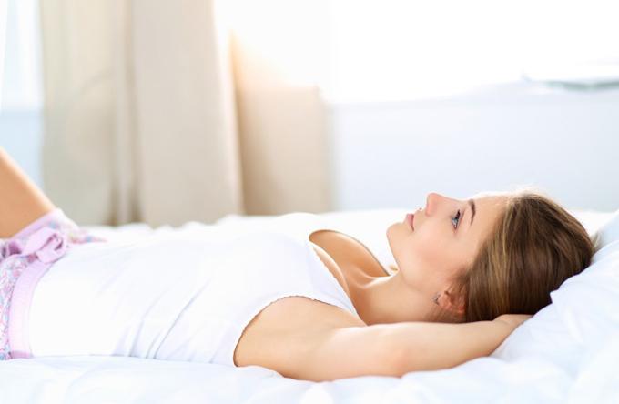 横になって考えている女性