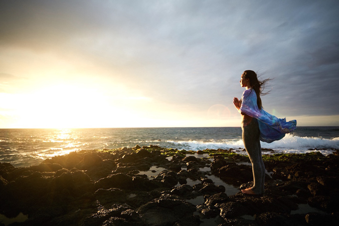 ハワイのキレイな夕焼けに向かって合掌しているアンジェラさん