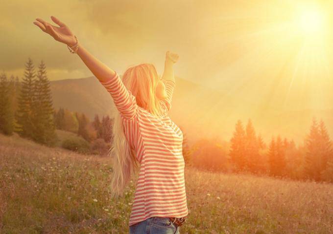 太陽に向かって手を伸ばす女性