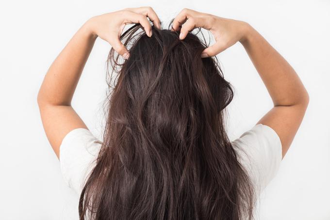 頭皮をマッサージしている女性の後ろ姿画像