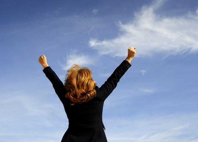 空に向かって背伸びをしている女性の後ろ姿の画像