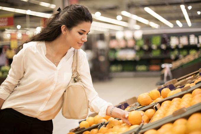 オレンジを選んでいる女性の画像